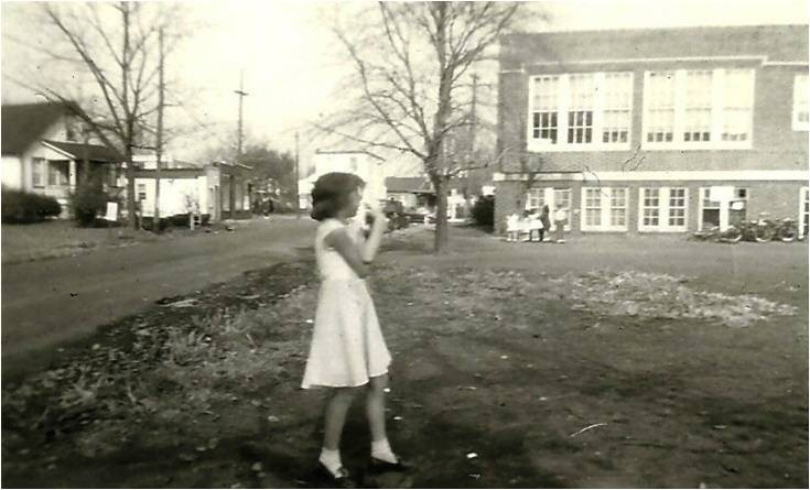 young girl outside of school house