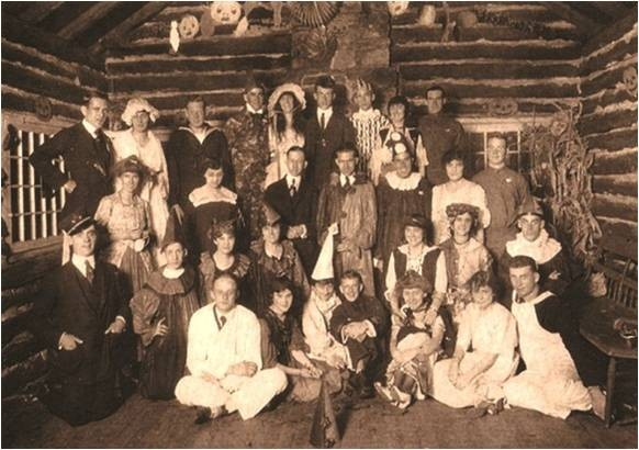 large family posing inside of a historic log cabin